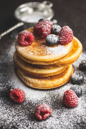 Sweet homemade pancakes with blueberries and raspberries sprinkled with sugar on old kitchen table. Archivio Fotografico - 139978852