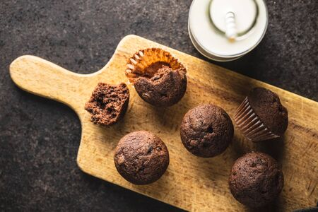 Tasty chocolate muffins. Sweet cupcakes on cutting board. Top view. Archivio Fotografico - 140155610