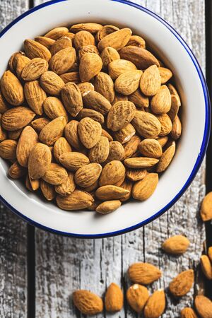 Dried almond nuts in bowl on old wooden table. Top view. Banque d'images - 142148554