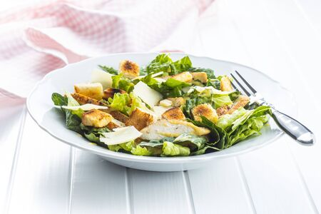 Chicken Caesar Salad with Cheese and Croutons on plate on white table.