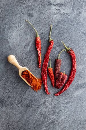 Dried red chili peppers and chili powder spice in wooden scoop. Top view.