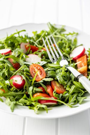 Fresh arugula salad with radishes, tomatoes and red peppers on plate. Imagens