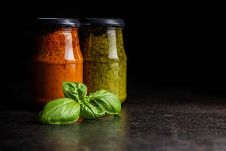 Green basil and red tomato pesto dip sauce in jar and basil leaves on black table.