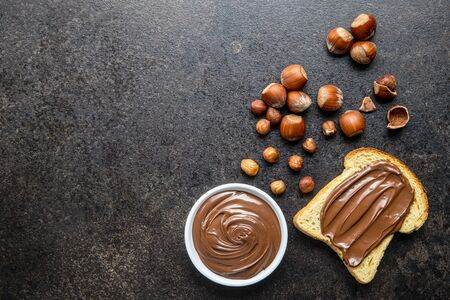Toast bread with hazelnut spread. Sweet chocolate cream on black kitchen table. Top view.