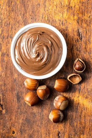 Sweet hazelnut spread. Chocolate cream in bowl on wooden table. Top view. Фото со стока
