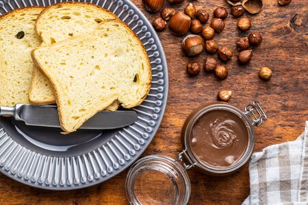Hazelnut spread and toast bread. Chocolate cream on wooden table. Top view. Фото со стока