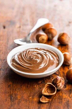 Sweet hazelnut spread. Chocolate cream in bowl on wooden table. Фото со стока