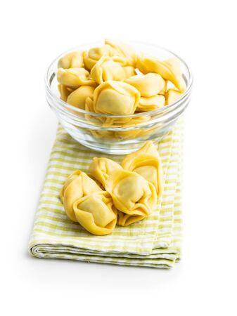 Tortellini pasta on checkered napkin. Italian stuffed pasta isolated on white background.