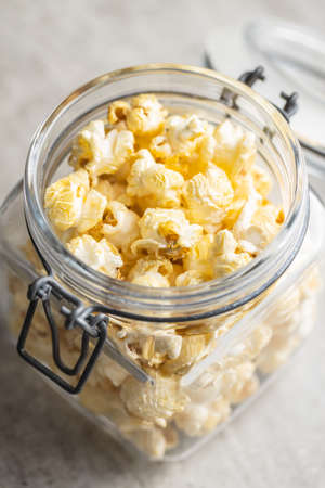 Sweet tasty popcorn in jar on kitchen table.