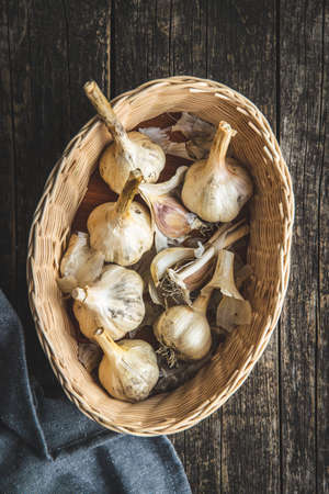 White garlic bulbs in basket on old wooden table and napkin. Top view.