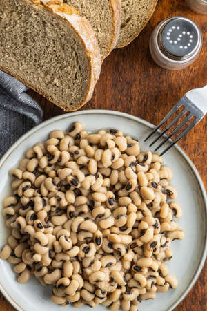 Marinated black eyed beans on plate with fork and bread. Top view.