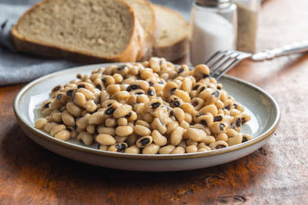 Marinated black eyed beans on plate with fork and bread.