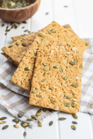 The crispy bread with pumpkin seeds. Knackebrot on white table. Banque d'images