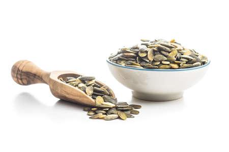 Peeled pumpkin seeds in wooden scoop isolated on white background.