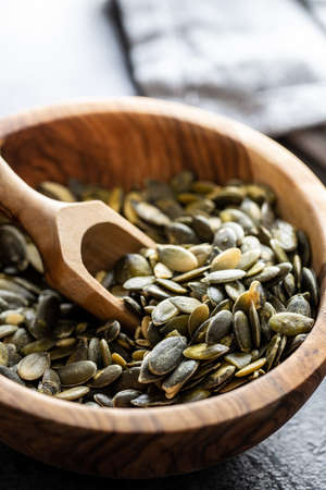 Peeled pumpkin seeds in wooden bowl and scoop on black table.