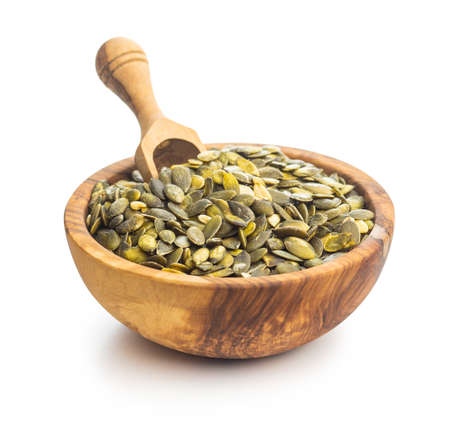 Peeled pumpkin seeds in wooden bowl with scoop isolated on white background.
