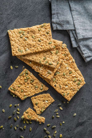 The crispy bread with pumpkin seeds. Knackebrot on black table. Top view. Banque d'images