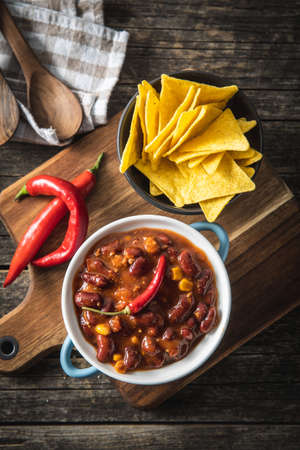 Chili with meat and tortilla chips. Mexican food with beans. Top view.
