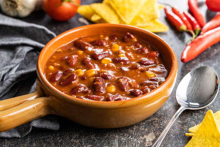 Chili with meat. Mexican food with beans in pot on black table. Banque d'images