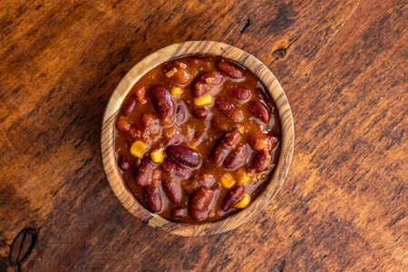 Chili with meat. Mexican food with beans in a wooden bowl. Top view.