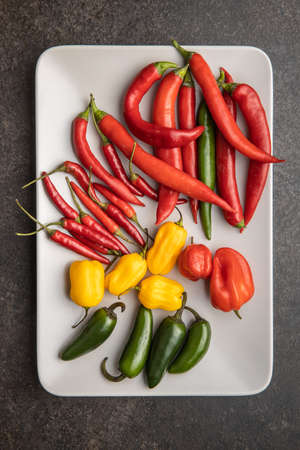 Various types of chili peppers. Chili, habanero and jalapeno peppers. Red, green and yellow hot peppers on plate. Top view. Banque d'images
