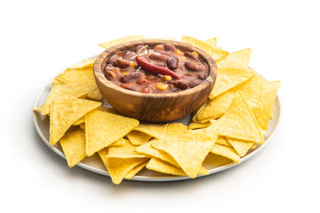 Chili with meat and tortilla chips on plate. Mexican food with beans in wooden bowl isolated on white background. Banque d'images