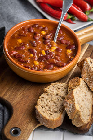 Chili with meat. Mexican food with beans in pot and bread on cutting board. Banque d'images