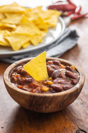 Chili with meat and tortilla chips. Mexican food with beans in a wooden bowl.