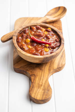 Chili with meat. Mexican food with beans in wooden bowl on white table.