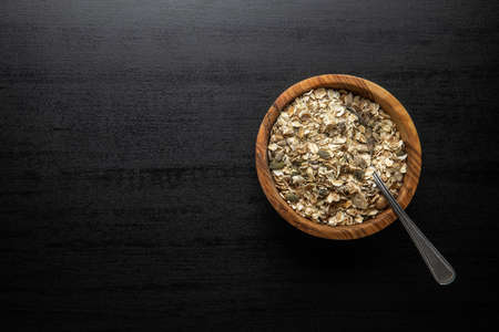 Muesli cereals. Healthy breakfast with oats flakes in bowl on black table. Top view. Banque d'images