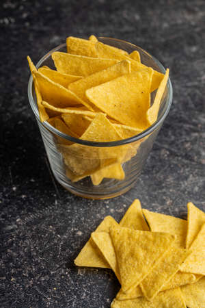 Salted tortilla chips on black table.