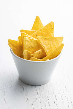 Salted tortilla chips in bowl on white table.
