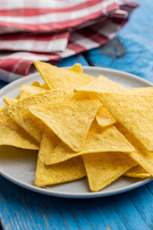 Salted tortilla chips on plate on blue table. Banque d'images
