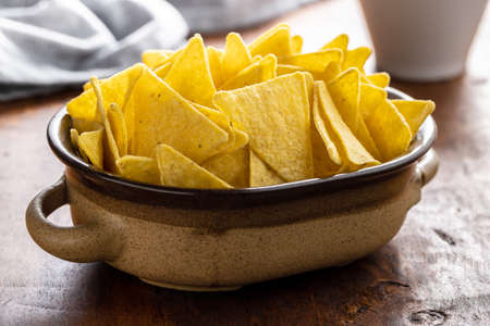 Salted tortilla chips in bowl on wooden table.