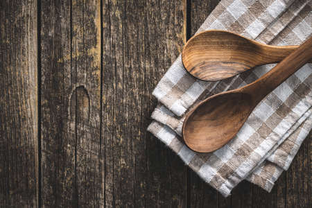Two wooden spoons on checkered napkin on old wooden table. Top view.