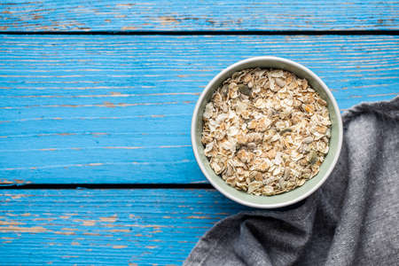 Muesli cereals. Healthy breakfast with oats flakes in bowl on blue wooden table. Top view.