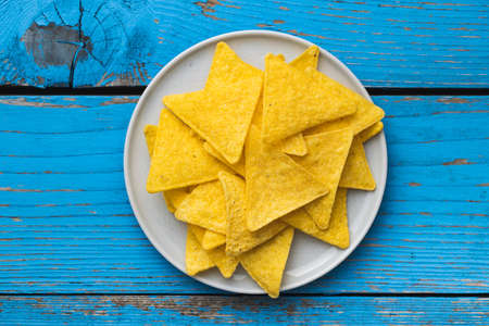 Salted tortilla chips on plate on blue table. Top view. Banque d'images