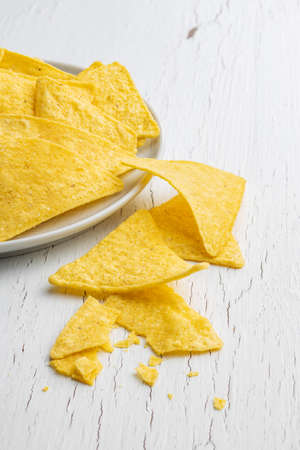Salted tortilla chips on white table.