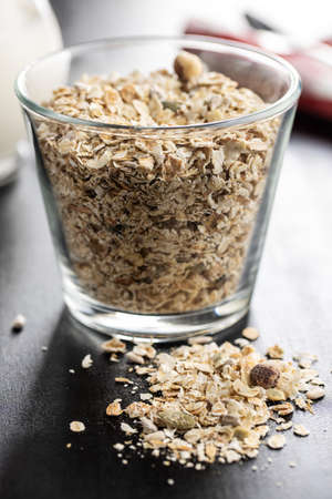 Muesli cereals. Healthy breakfast with oats flakes on black table.