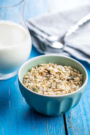 Muesli cereals. Healthy breakfast with oats flakes in bowl on blue wooden table.