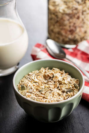 Muesli cereals. Healthy breakfast with oats flakes in bowl on black table.