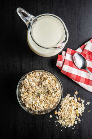 Muesli cereals. Healthy breakfast with oats flakes and milk on black table. Top view.