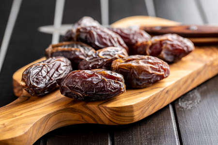 Dried dates fruit on cutting board on black wooden table.