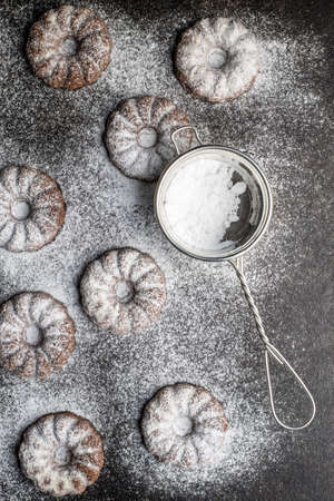 Sweet rings cookies. Biscuits with cocoa flavor sprinkled with sugar on black table. Top view.