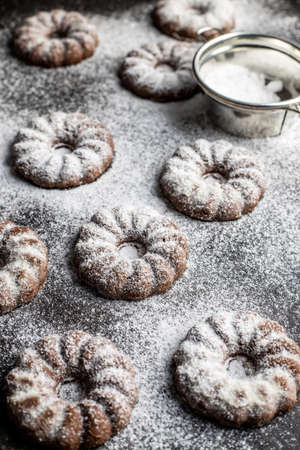 Sweet rings cookies. Biscuits with cocoa flavor sprinkled with sugar on black table. 免版税图像