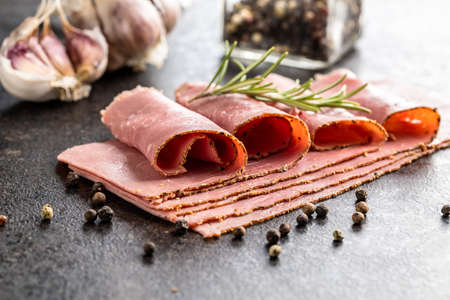 Sliced beef ham on black table. Imagens