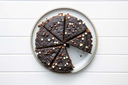 Sweet chocolate cake on plate on white table. Top view. Imagens