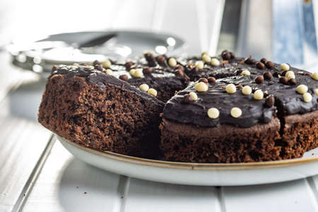 Sweet chocolate cake on plate on white table. Imagens