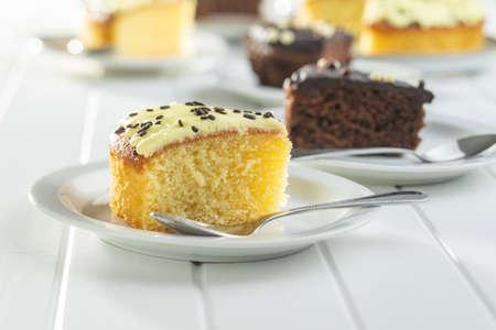 Piece of lemon cake on dessert plate on white table.