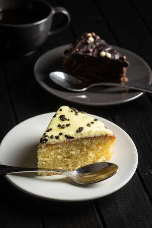 Piece of lemon and chocolate cake on dessert plate on black table. Imagens